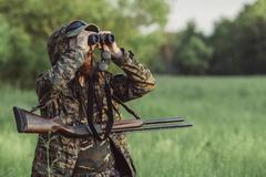 Hunter looking through binoculars on grassy field Stock Photos