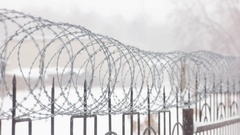 Barbed wire on metal fence with pointed rods. Snowing weather. Stock Footage