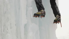 Boots with crampons in Ice climbing the icicle. Slow motion. Stock Footage