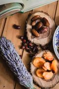 Book and dried fruits on wooden plates Stock Photos