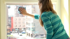 Housekeeper woman clean window with rag at home Stock Footage