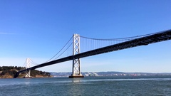 View from over water of Golden Gate Bridge and mountains Stock Footage