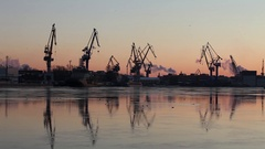 Silhouettes of of portal cranes on the horizon Arkistovideo