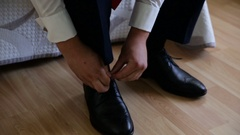 Groom putting his wedding shoes. Hands of wedding groom getting ready in suit Stock Footage