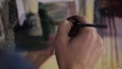 Close-up of the hands of an artist who paints a picture Stock Footage