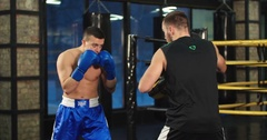 Boxer training uppercut punches in boxing club 4k video. Fighter with trainer Stock Footage