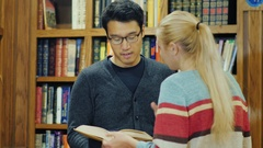 Friends talking in the college library. Asian man and Caucasian woman attractive Stock Footage