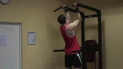 Muscular man doing pull ups while working out in gym. Stock Footage