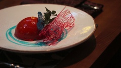 Close up of a deserd served on a white plate with a strawberry sauce. Stock Footage