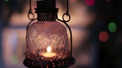 A vintage lantern with a candle on a background of Christmas lights Stock Footage