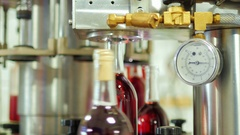 Bottles of red alcohol stoppered. In the foreground conveyor element - gauge Stock Footage