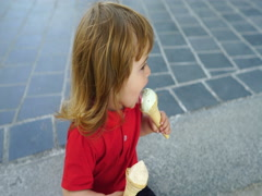 Curly-haired child toddler eating two ice cream on the street Stock Footage