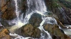 A tropical waterfall flows through a dense rainforest Stock Footage