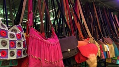 Female hand chooses handbags at night market Stock Footage