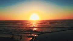 Beautiful timelapse of the sunset on the beach with people partying Stock Footage
