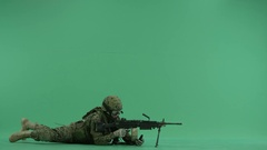 Soldier lying and targeting to the right at green screen Stock Footage