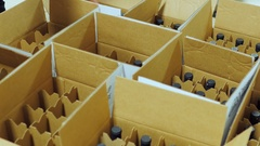 Bottles of wine are placed in cardboard boxes. Top view Stock Footage