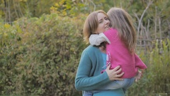Little daughter with her mother walking in autumn forest - mom shows daughter Stock Footage