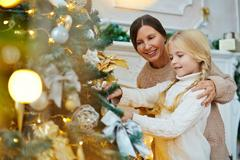 Little girl and her granny decorating xmas tree together Stock Photos