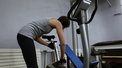 A young girl is getting ready for a workout on a exercise bike Stock Footage