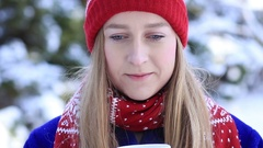 Young woman enjoying scent of coffee in wintertime Stock Footage