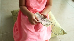 Little girl counts dollars banknotes indoor. 4K Stock Footage