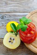 Jam from quince and sprig of mint in a glass jar. Stock Photos