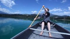 Caucasian woman in canoe drinking beverage, Jasper, Alberta, Canada Stock Footage