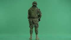 Soldier moving hands standing back at green screen Stock Footage