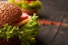 Two hamburger on a wooden table Stock Photos