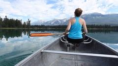 Caucasian woman paddling in canoe, Jasper, Alberta, Canada Stock Footage