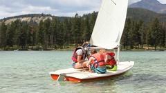 Caucasian boys and girl sailing on lake, Jasper, Alberta, Canada Stock Footage