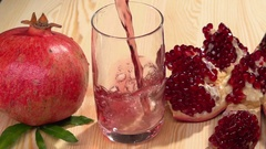 Garnet. Fresh pomegranate juice is pouring into a glass on a wooden table. Stock Footage