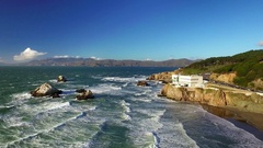 Aerial view of waves crashing on beach and mountains in San Francisco Stock Footage