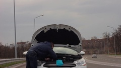 Stranded man with broken down car looks under the bonnet. Stock Footage