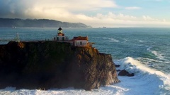 Aerial view of lighthouse overlooking giant ocean waves under evening sky 2 Stock Footage