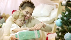 Laughing mother open Christmas presents with her baby girl 1 year old sitting in Stock Footage
