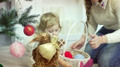 Young mother plays with her baby girl under the Christmas tree. Holiday season Stock Footage