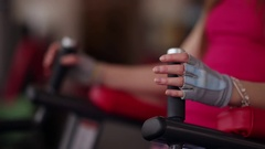 Midsection of a woman exercising legs while doing I-sits on parallel bar in the Stock Footage