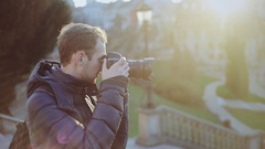 Young man photographer taking photo with his camera on european street Stock Footage