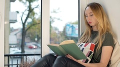 Sad girl sitting by the window and reading some publication Stock Footage