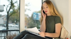 Girl looking worried while talking on cellphone about her bills Stock Footage