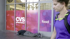 Bicylists walkig past homeless man lying down sleeping on street LA California Stock Footage