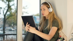 Girl wearing headphones and watching funny video on tablet Stock Footage