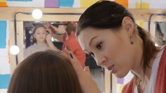 Professional makeup artist applies makeup to a beautiful model. Colors eye Stock Footage