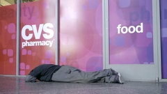 Homeless man sleeping on sidewalk with CVS Pharmacy and food sign in LA Stock Footage