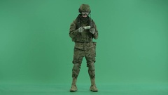 Soldier standing and giving money to camera at green screen Stock Footage