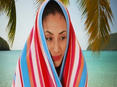 A Latina woman relaxes on the beach with a towel wrapped around her Stock Footage