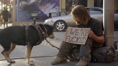 Homeless man with beard throwing treat to pet dog on street with funny sign LA Stock Footage