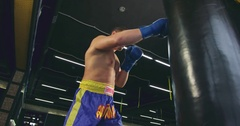 Boxer training punching bag 4k video. Fighter defense block punches jab series Stock Footage